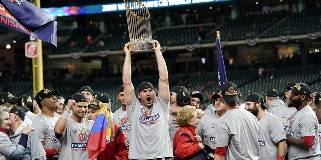 Washington Nationals catcher Yan Gomes celebrates the the trophy after Game 7 of the baseball World Series against the Houston Astros Wednesday, Oct. 30, 2019, in Houston. The Nationals won 6-2 to win the series.