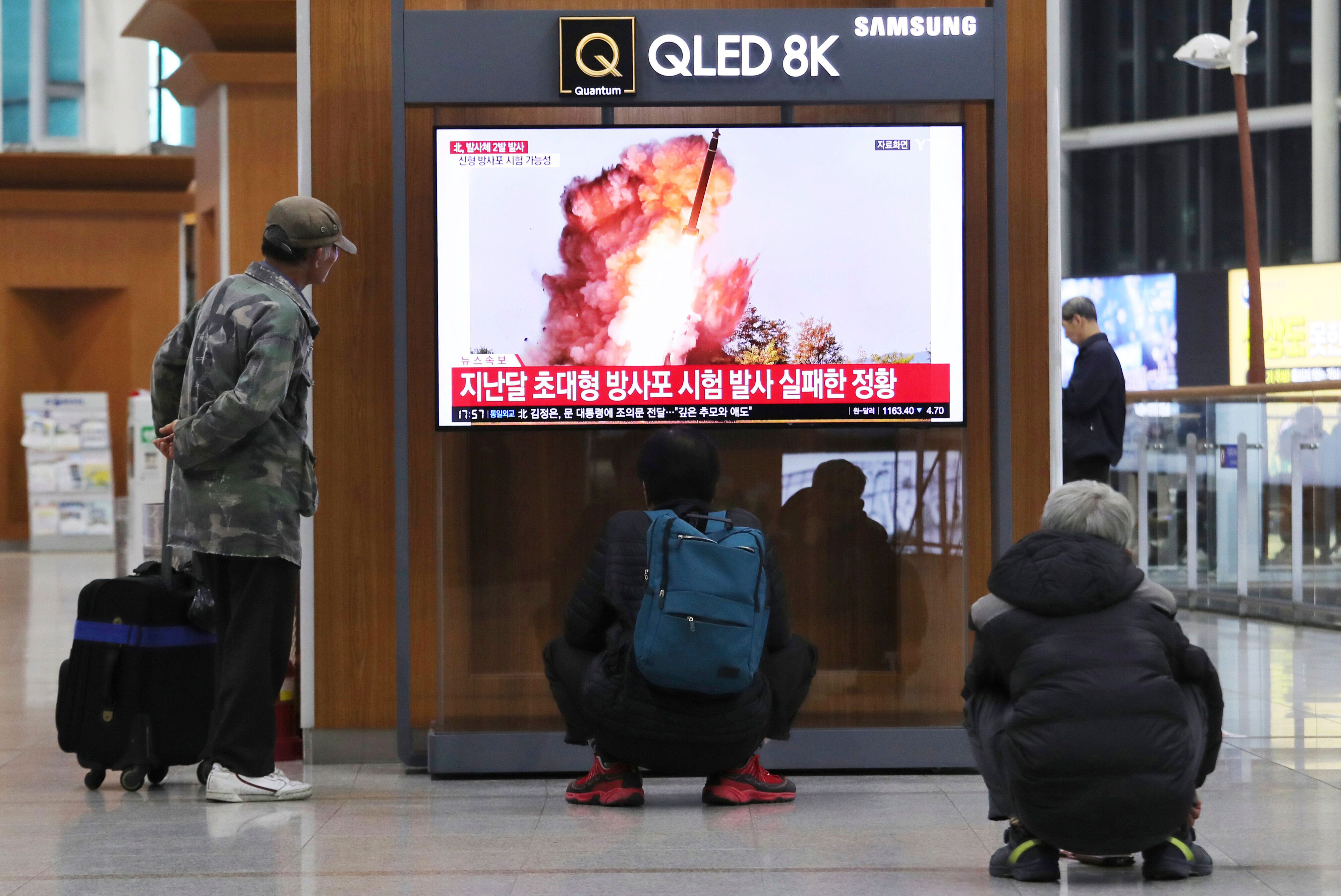 People watch a TV showing a file image of an unspecified North Korea's missile launch during a news program at the Seoul Rail