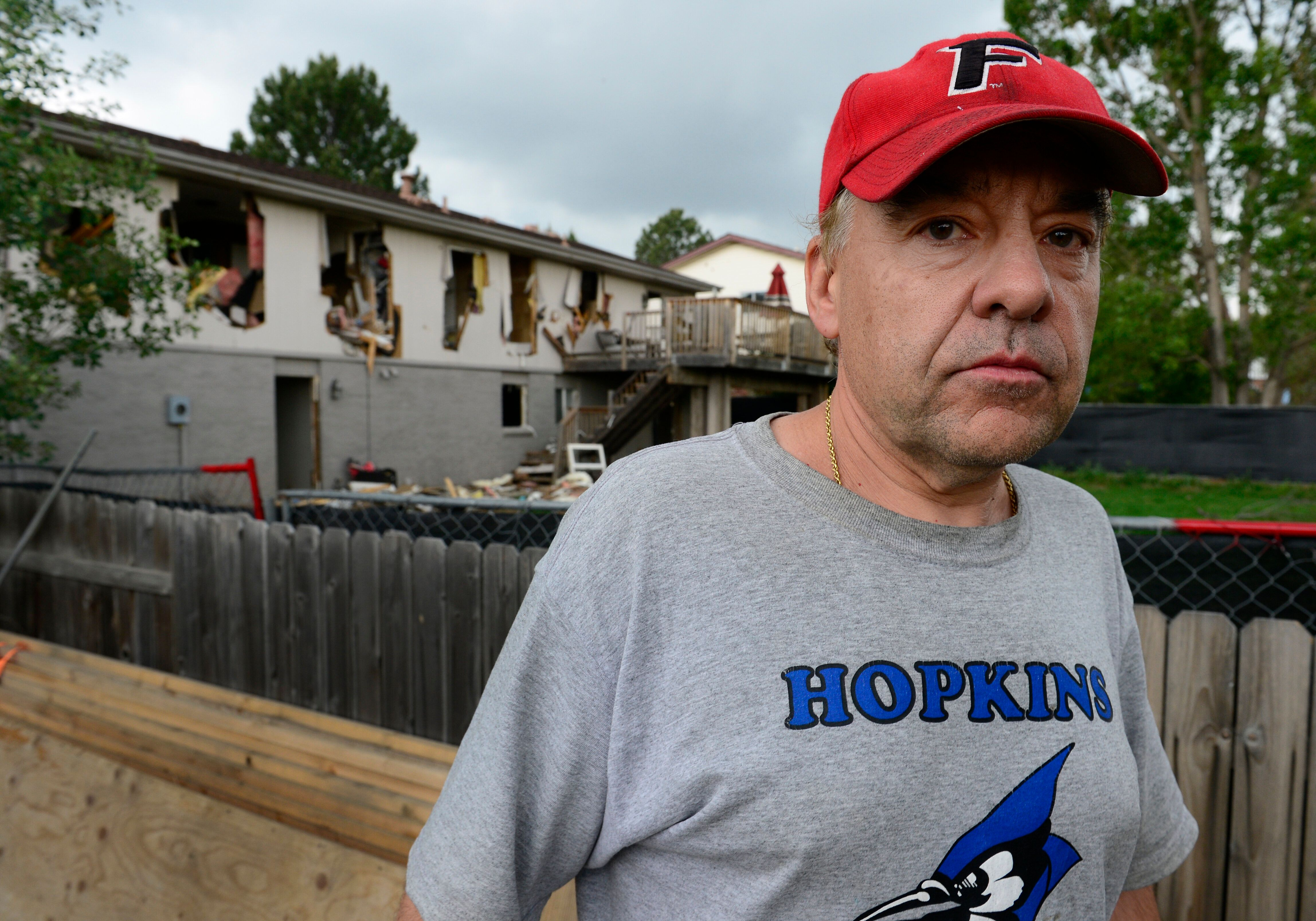 Leo Lech stands on a pile of wood in his neighbor's yard that overlooks the back of his condemned home in June 2015.