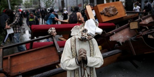 A damaged statue taken from a church forms part of barricade created by anti-government protesters, in Santiago . (AP Photo/Esteban Felix)