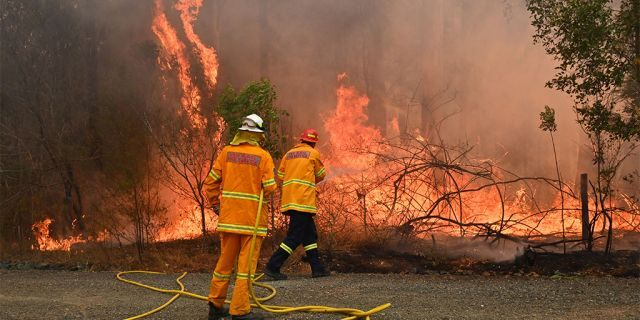 Firefighters tackle a bushfire to save a home in Taree, 350km north of Sydney on November 9, 2019 as they try to contain dozens of out-of-control blazes that are raging in the state of New South Wales. - At least two people have died and 100 homes have been destroyed as an unprecedented number of bushfires tore through eastern Australia. (Photo by PETER PARKS / AFP) (Photo by PETER PARKS/AFP via Getty Images)