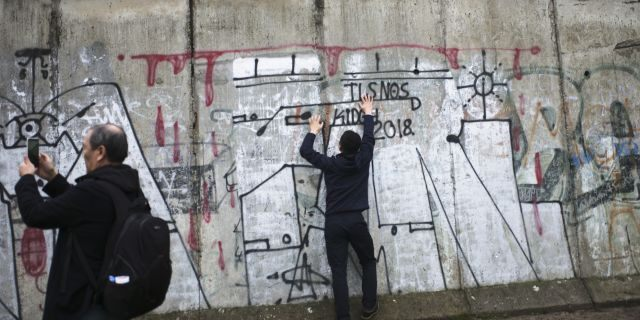 Tourist take photos at remains of the Berlin Wall after commemorations celebrating the 30th anniversary of the fall of the Berlin Wall at the Wall memorial site at Bernauer Strasse in Berlin, Saturday, Nov. 9, 2019.