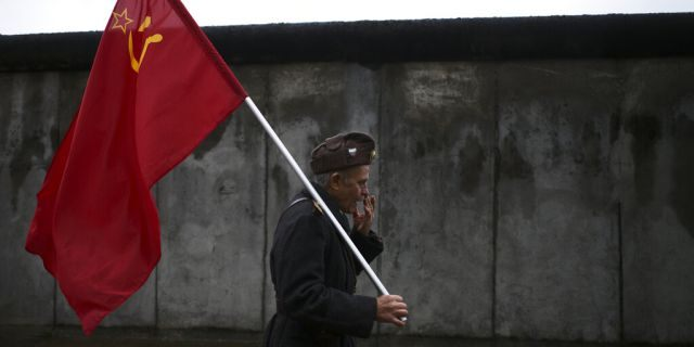 An elderly man with a Soviet flag walks in front of remains of the Berlin Wall after commemorations celebrating the 30th anniversary of the fall of the Berlin Wall at the Wall memorial site at Bernauer Strasse in Berlin, Saturday, Nov. 9, 2019. The man, who would not give his name, walks around with the flag as a protest against capitalism.