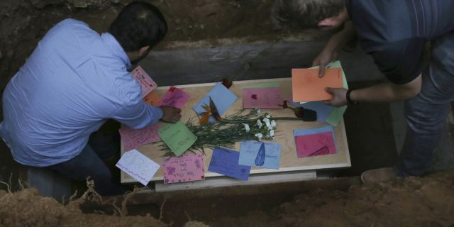 Men arrange personal notes on the coffin that contains the remains of 12-year-old Howard Jacob Miller Jr., at the cemetery in Colonia Le Baron, Mexico, Friday, Nov. 8, 2019, during a burial service for Rhonita Miller and four of her young children, who were murdered by drug cartel gunmen.(AP Photo/Marco Ugarte)