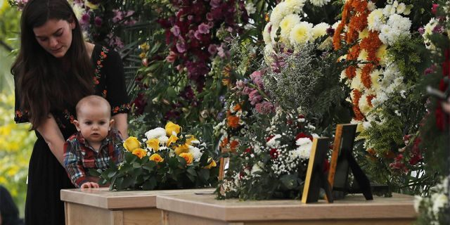 A woman and child stood by the coffins of Dawna Ray Langford, 43, and her sons Trevor, 11, and Rogan, 2, who were killed by drug cartel gunmen on Monday. (Associated Press)