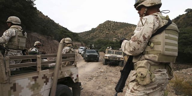 Heavily armed Mexican authorities guarded a caravan of friends and relatives as they arrived at the site where nine Americans were gunned down on Monday. (Associated Press)