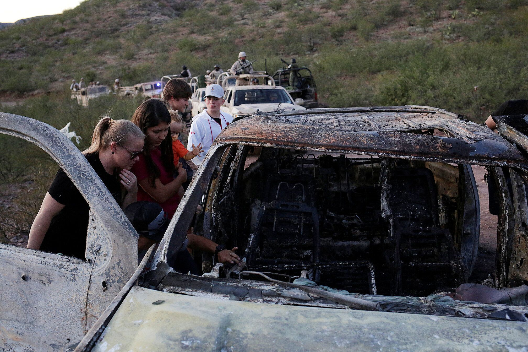 Relatives of slain members of Mexican-American families belonging to Mormon communities observe the burnt wreckage of a vehic