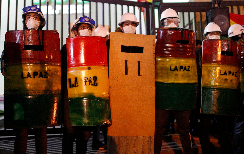 Demonstrators with makeshift shields protest against President Evo Morales' reelection, in La Paz, Bolivia, Saturday, Nov. 9,