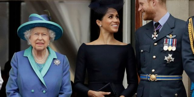 "In this Tuesday, July 10, 2018 file photo Britain's Queen Elizabeth II, and Meghan the Duchess of Sussex and Prince Harry watch a flypast of Royal Air Force aircraft pass over Buckingham Palace in London. As part of a surprise announcement distancing themselves from the British royal family, Prince Harry and his wife Meghan declared they will ""work to become financially independent"" — a move that has shocked the world."