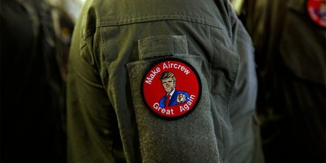 "A service member wears a patch that says ""Make Aircrew Great Again"" as they listen to President Donald Trump speak to troops at a Memorial Day event aboard the USS Wasp in Yokosuka, Japan. The patch includes a likeness of Trump. (AP Photo/Evan Vucci)"