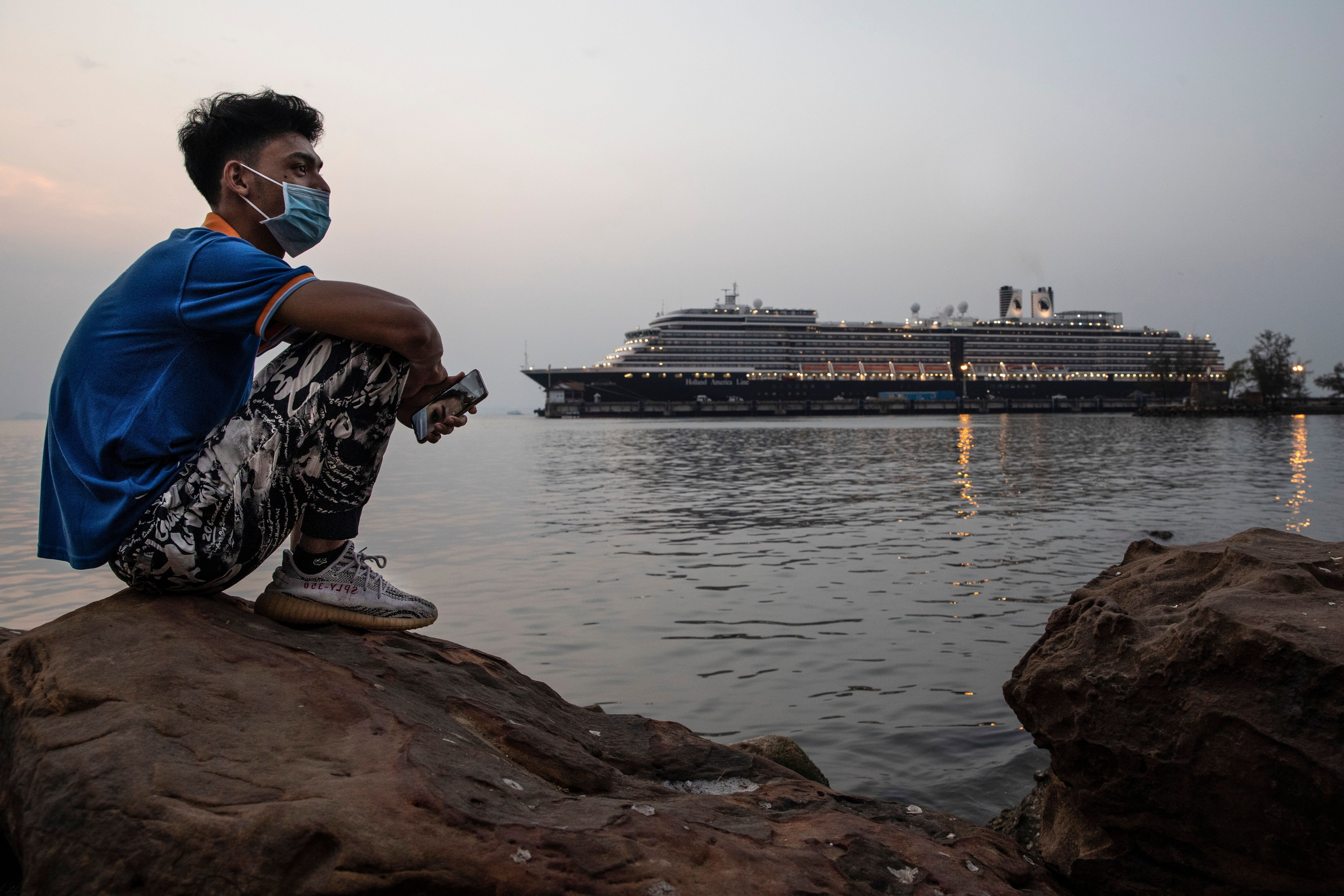 A Cambodian man sits by the ocean near the docked MS Westerdam cruise ship in Sihanoukville, Cambodia, on Monday. The cruise