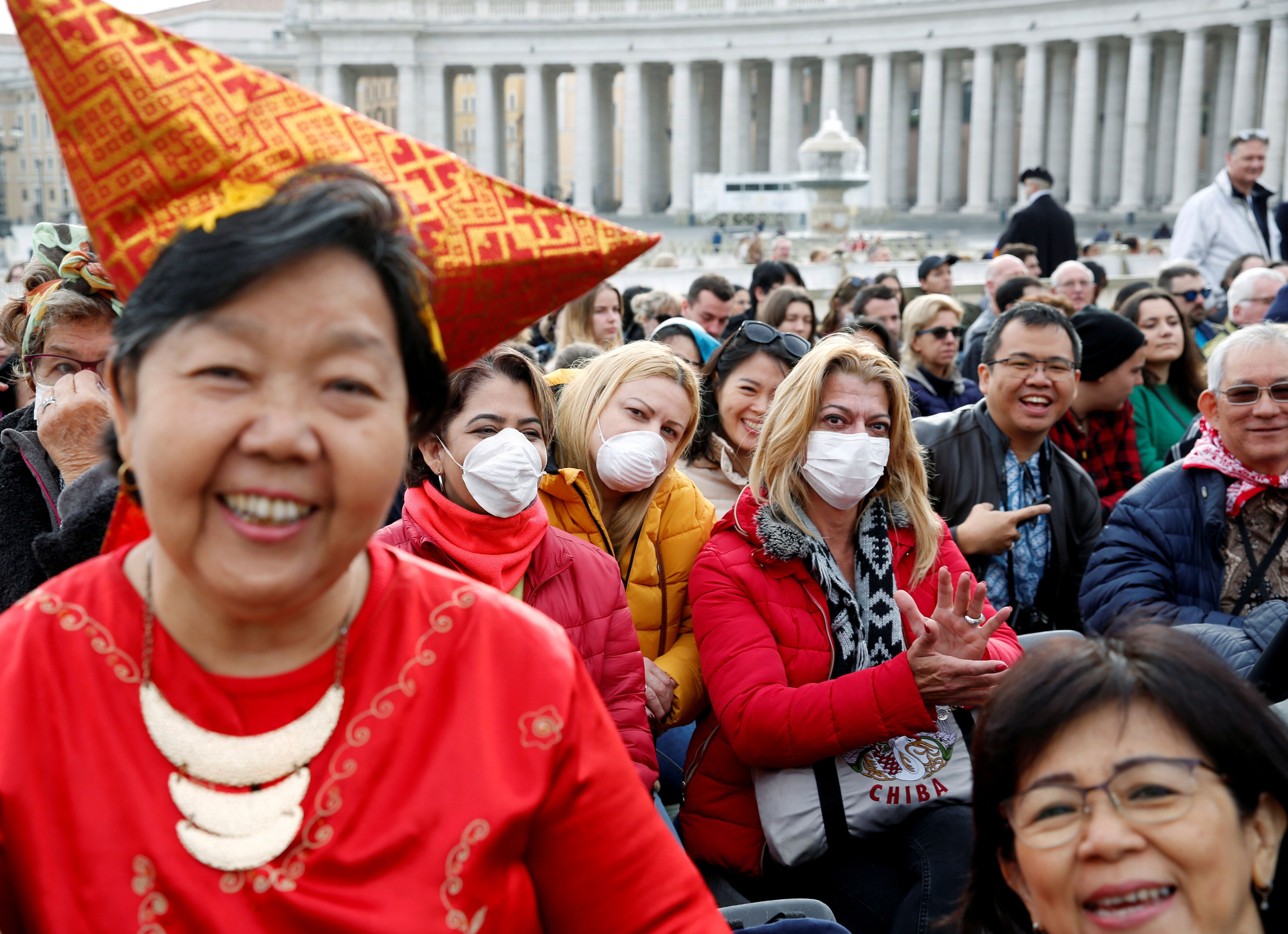 People, a few in face masks, wait for Pope Francis to arrive for his weekly general audience at the Vatican.