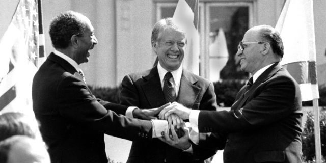 Egyptian President Anwar Sadat, left, U.S. President Jimmy Carter, center, and Israeli Prime Minister Menachem Begin clasp hands on the north lawn of the White House after signing the peace treaty between Egypt and Israel on March 26, 1979. (AP Photo/ Bob Daugherty)