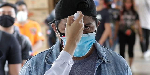 Temperatures are checked before people enter a local city hall during a community quarantine aimed to prevent the spread of the new coronavirus in Manila, Philippines, Tuesday.