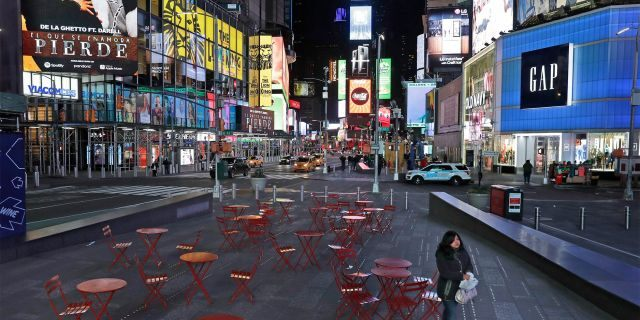 A woman walks through a lightly trafficked Times Square in New York, Monday, March 16, 2020. (AP Photo/Seth Wenig)