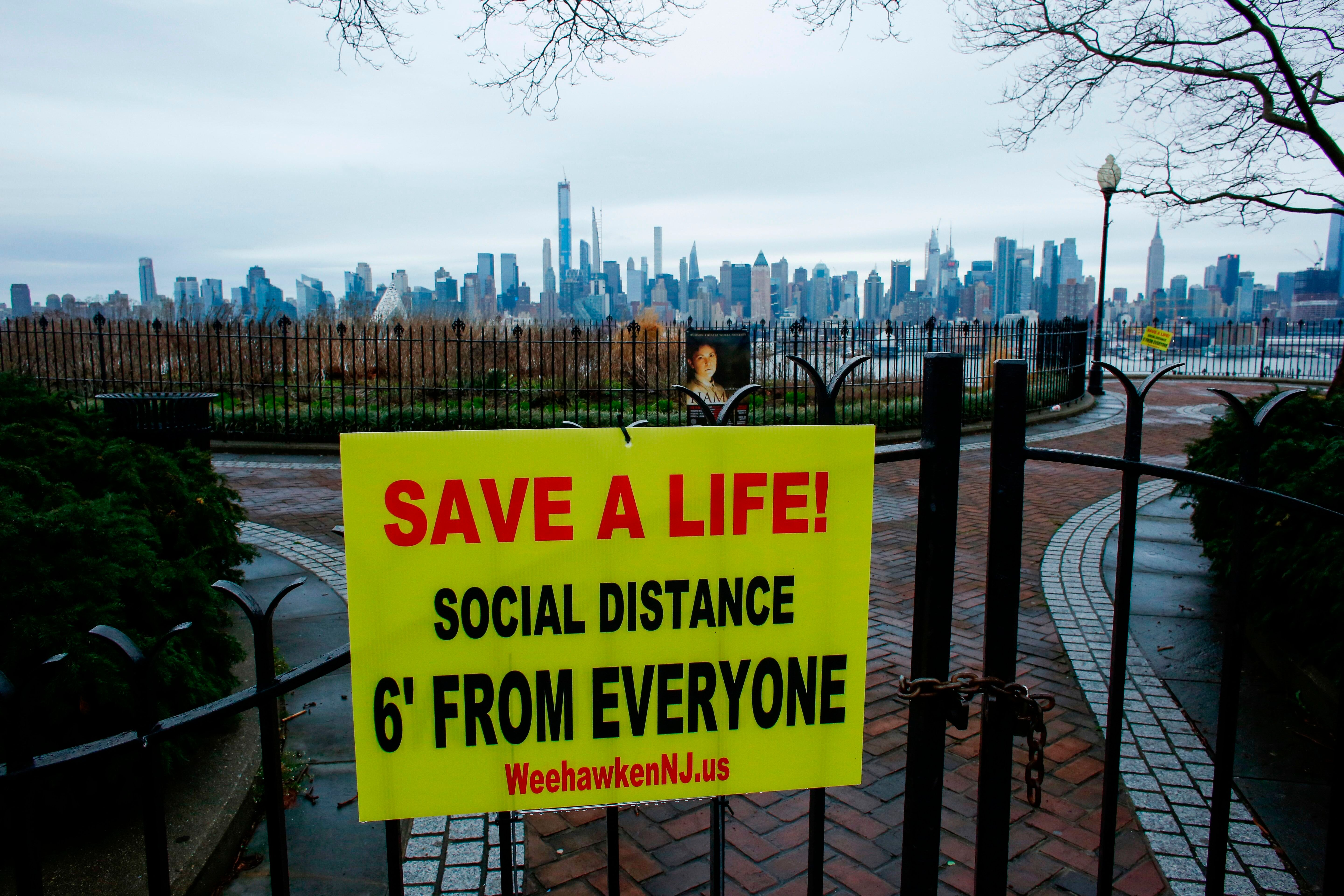 A sign encouraging social distancing to stop the spread of coronavirus is displayed at a closed park in Weehawken, New Jersey
