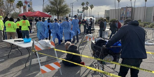 People wait to be screened before entering a homeless shelter set up in a parking lot in Las Vegas on Saturday.