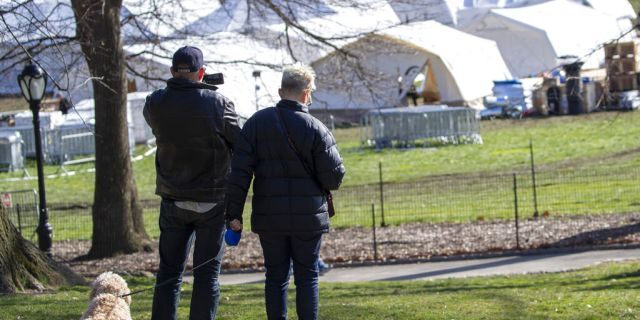 A couple pauses to take a picture of the Samaritan's Purse field hospital as they walk their dog in New York's Central Park, Wednesday, April 1, 2020. The new coronavirus causes mild or moderate symptoms for most people, but for some, especially older adults and people with existing health problems, it can cause more severe illness or death.