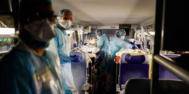 Medical staff evacuate patients infected with the COVID-19 virus aboard a high-speed train at the Gare d'Austerlitz train station Wednesday in Paris. (Thomas Samson, Pool via AP)