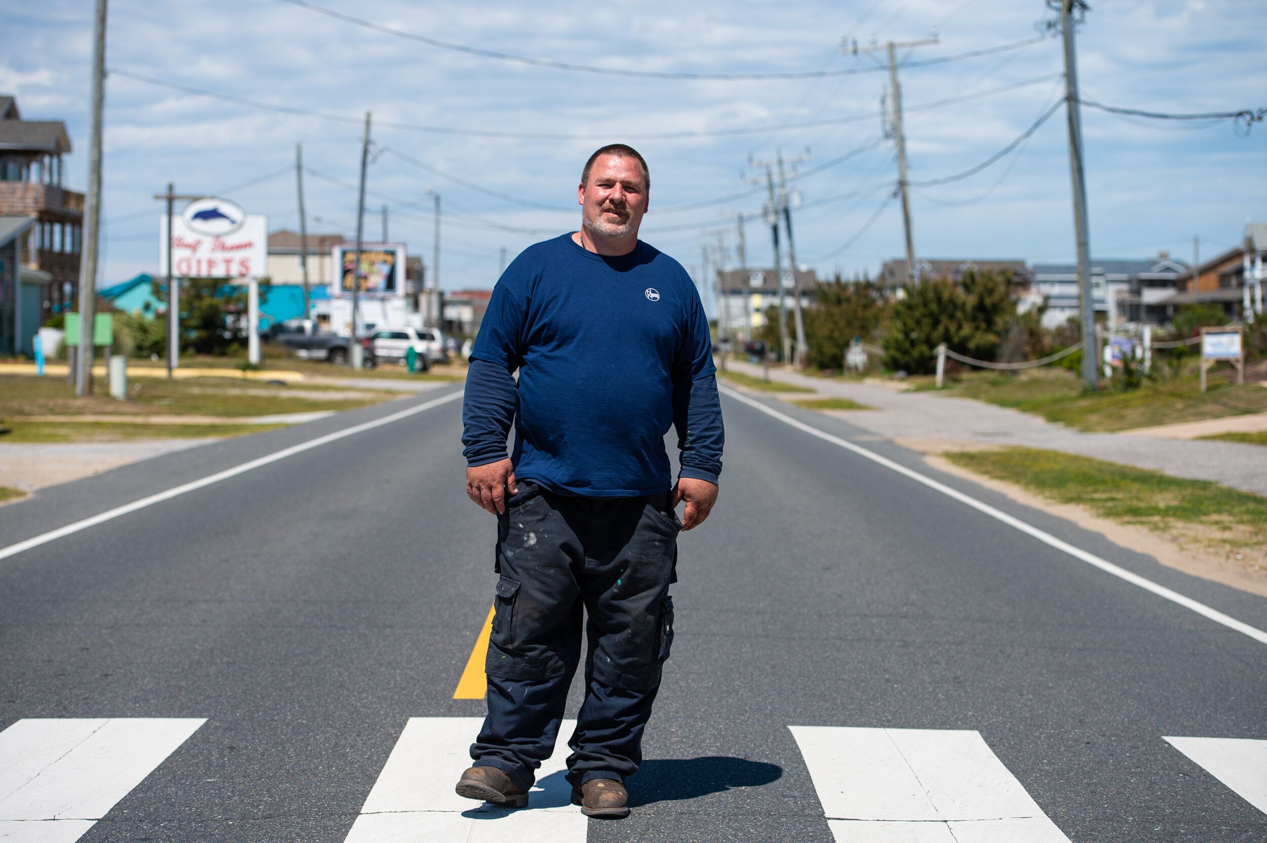 """Joseph Bakersmith, a Dare County resident, plumber and newly dubbed """"essential worker,"""" poses on a deserted """"beach road"""" (Sou"""