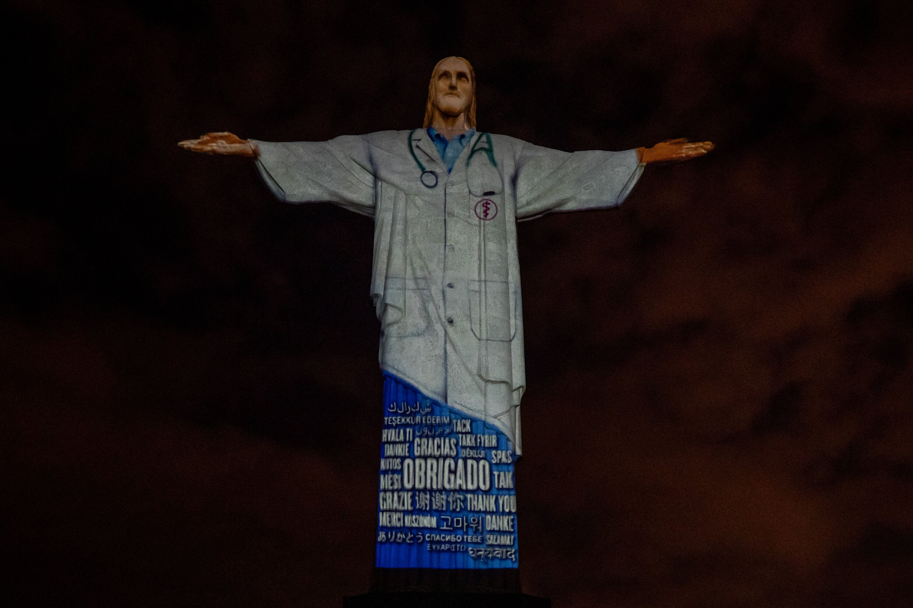 """View of the illuminated statue of Christ the Redeemer that reads """"Thank you"""" in many languages on April 12."""