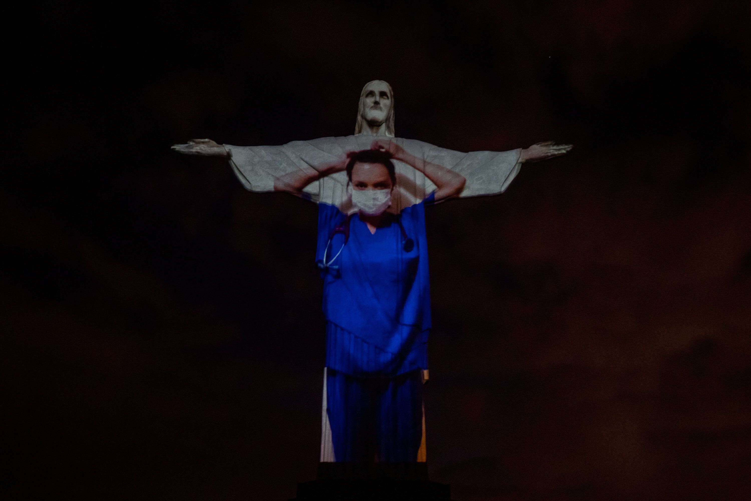 View of a medical worker on the illuminated statue of Christ the Redeemer.