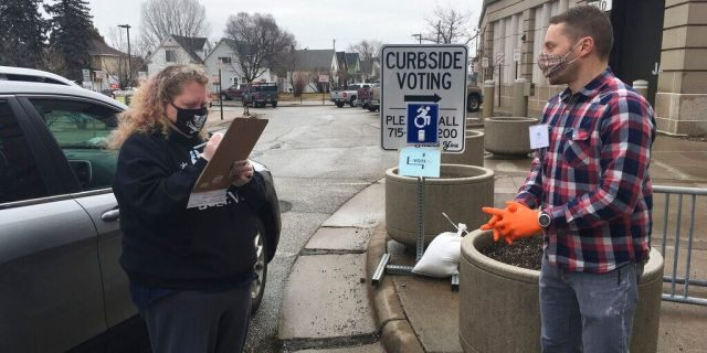 Richard Kaufman, right, a volunteer election official in Superior Wis., helps Betty Bockovich cast a vote at a curbside voting station set up outside the Government Center in Superior, Wis., Tuesday, April 7, 2020. Voters could ring a doorbell and poll workers would come outside to help them vote in the state's presidential primary election if they didn't want to go inside to cast their ballots because of the COVID-19 outbreak. (Dan Kraker/Minnesota Public Radio via AP)