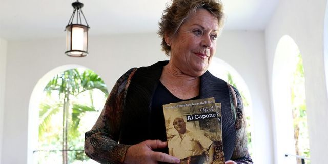 Deirdre Marie Capone, the last living relative of Al Capone to carry his name, holds a copy of the book she wrote about her uncle as she visits his former home during a tour of the historic house on March 18, 2015, in Miami Beach, Fla.
