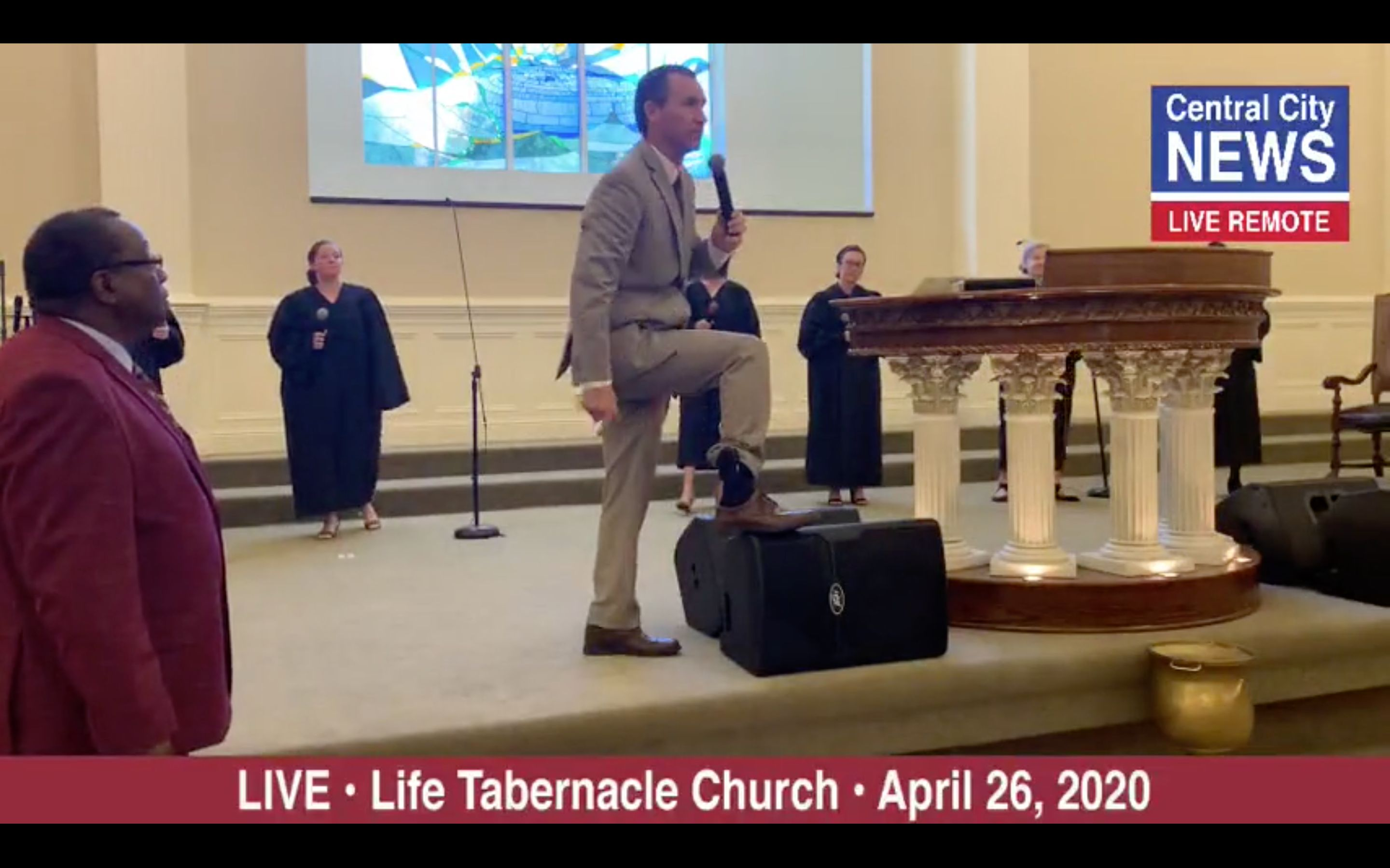 Pentecostal preacher Tony Spell shows off his ankle monitor during a church service on Sunday. Spell is under house arrest fo