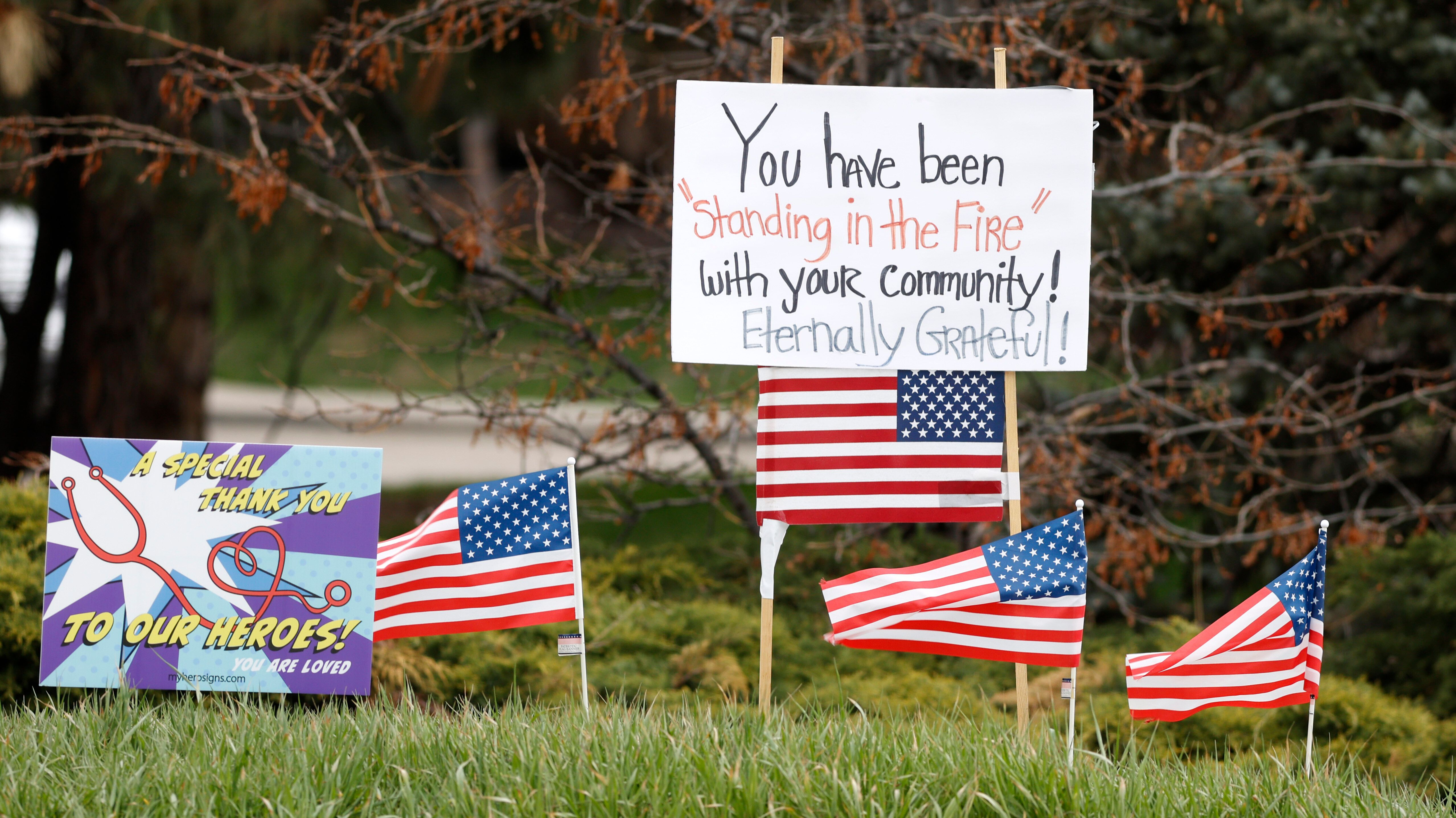 Signs and U.S. flags stand in honor of healthcare workers, across from Littleton Adventist Hospital on Sunday, April 26, 2020