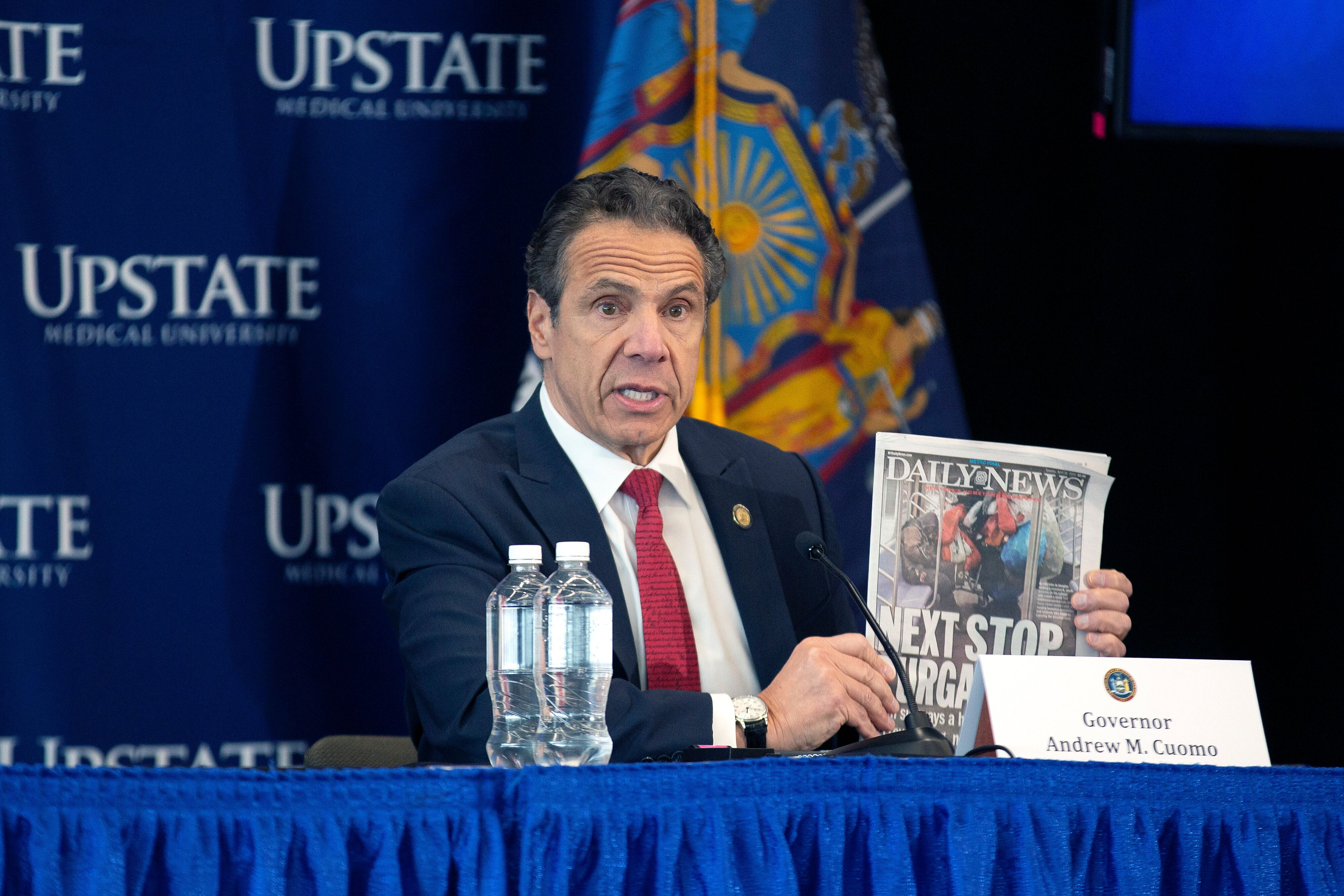 New York Gov. Andrew Cuomo holding up an article about problems with homeless people riding the subway.