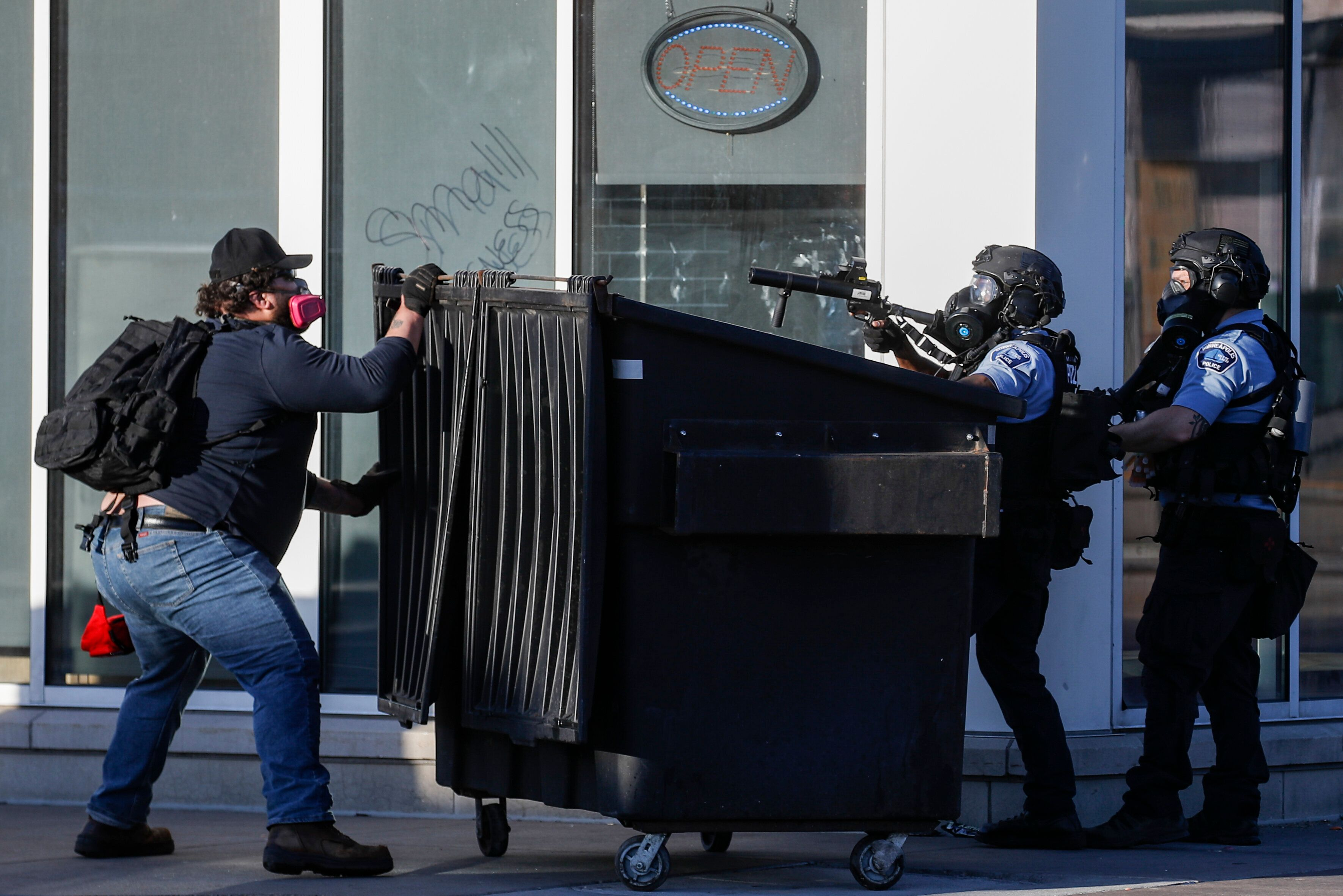 A protestor faces off with two police officers using less-lethal ammunition in their weapons, Thursday, May 28, 2020, in St.