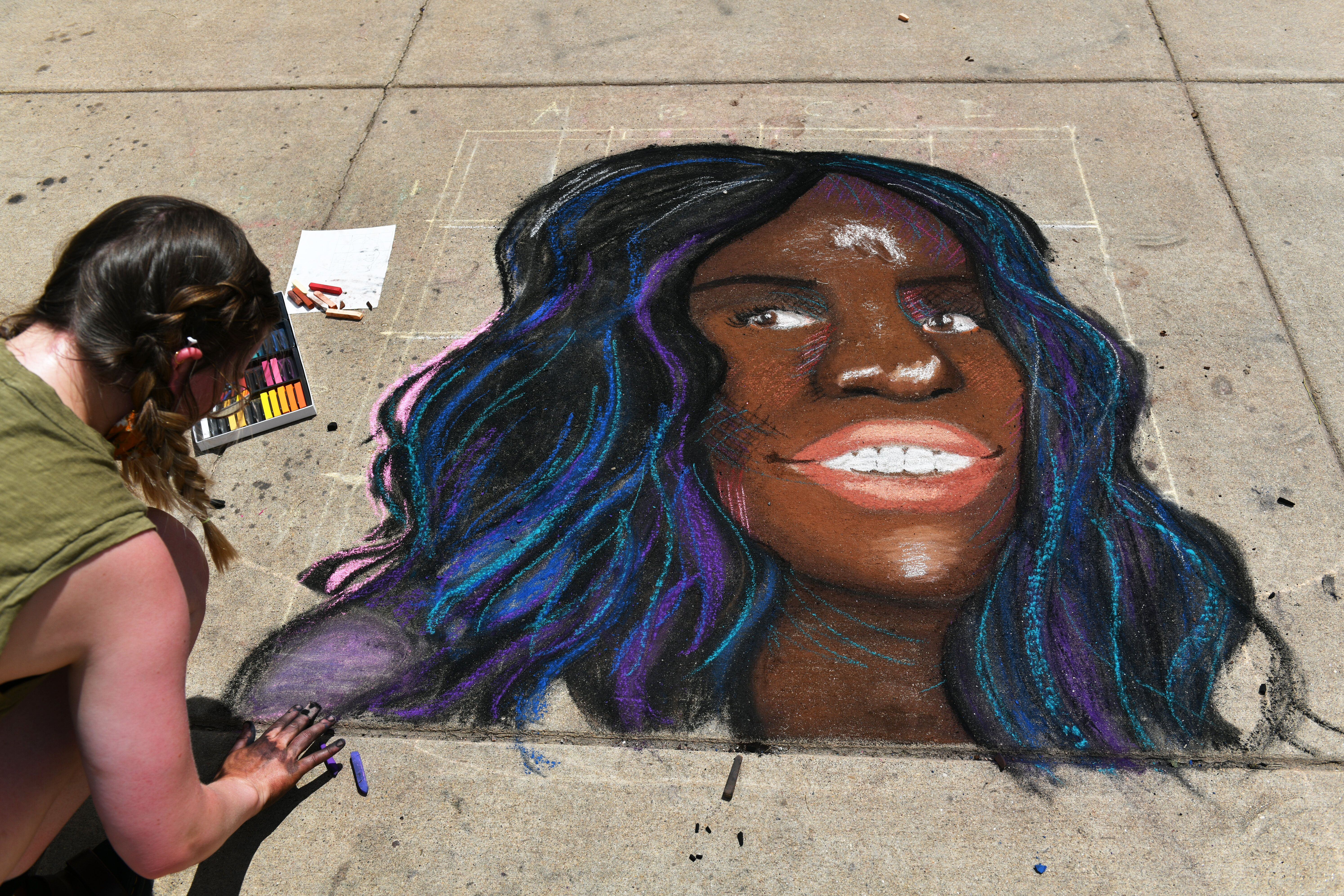 An artist drawing a portrait of Breonna Taylor in front of the Colorado State Capitol building in Denver on June 5.