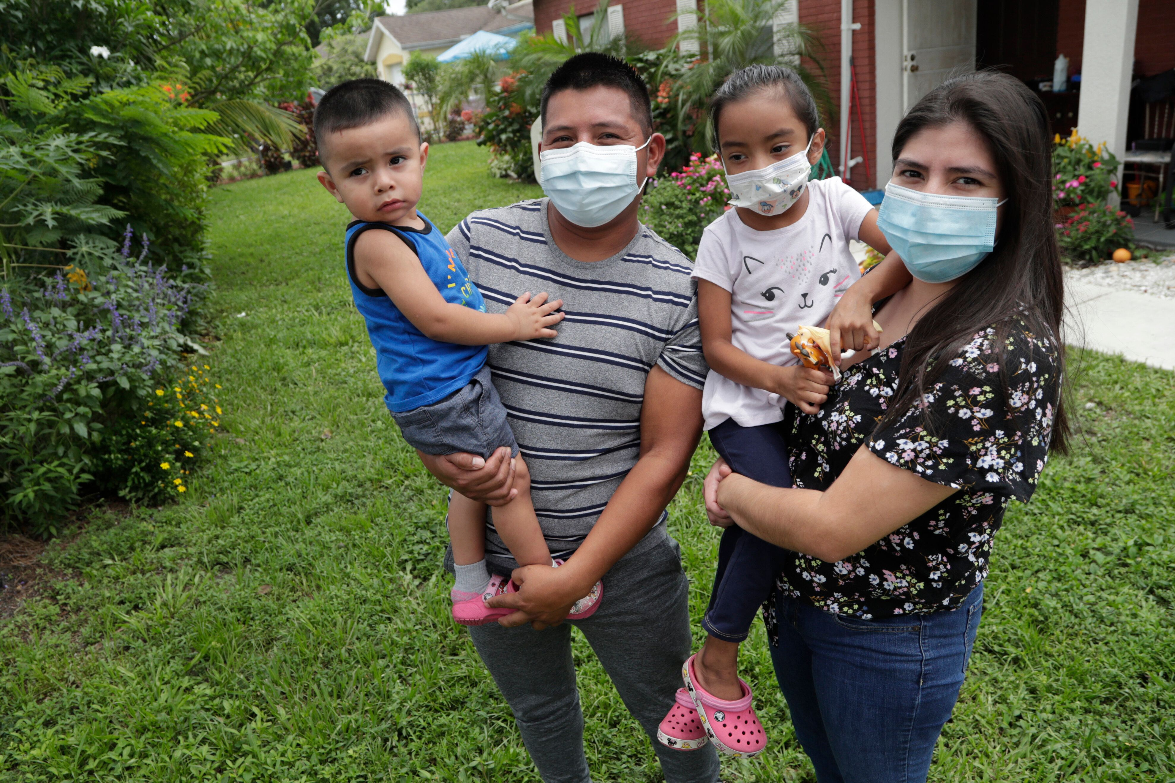 Elbin Sales, second from left, poses for a photograph with his wife, Yecenia Solorzano, right, and children Jordi Sales, left