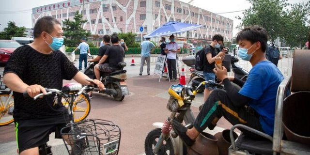People wearing face masks to protect against the new coronavirus stop at a checkpoint outside the Xinfadi wholesale food market district in Beijing, Saturday, June 13, 2020. Beijing closed the city's largest wholesale food market Saturday after the discovery of seven cases of the new coronavirus in the previous two days.