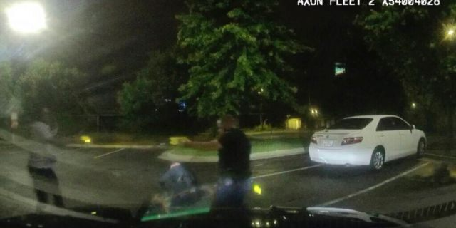 Dashboard camera video provided by the Atlanta Police Department shows Rayshard Brooks, left, and Officer Garrett Rolfe pointing Tasers at one another, while Officer Devin Brosnan is seen getting up after a struggle among the three men in the parking lot of a Wendy's restaurant.