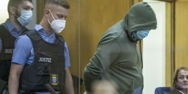 "Police officers lead defendant Markus H., right, into the court room in Frankfurt, German, June 16, 2020. The Higher Regional Court begin hearing the case against two far-right extremists accused of killing the regional politician Walter Luebcke of Merkel""s Christian Democratic Union party. (Thomas Lohnes/Pool via AP)"