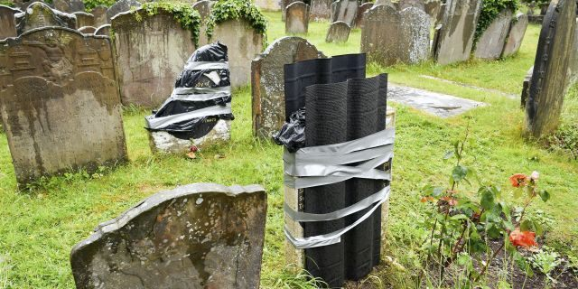 """The damaged headstone and footstone on the grave of an enslaved African man, in St Mary's churchyard, in Bristol, England, Thursday June 18, 2020, which have been vandalized in an apparent """"retaliation attack"""" following the toppling of a statue of slave trader Edward Colston during anti-racist protests held in the wake of the killing of George Floyd in the US. The Grade II-listed, brightly painted memorial to Scipio Africanus have been smashed and a message was scrawled in chalk on flagstones nearby. (Ben Birchall/PA via AP)"""