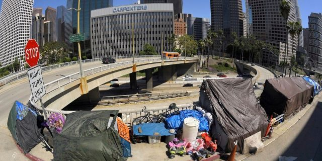 This file photo shows a homeless encampment at the corner of Wilshire Boulevard and Beaudry Avenue along the 110 Freeway during the coronavirus outbreak in downtown Los Angeles. A judge has approved an agreement in which the city and county of Los Angeles will provide housing for almost 7,000 homeless people who live near freeways. (AP Photo/Mark J. Terrill, File)