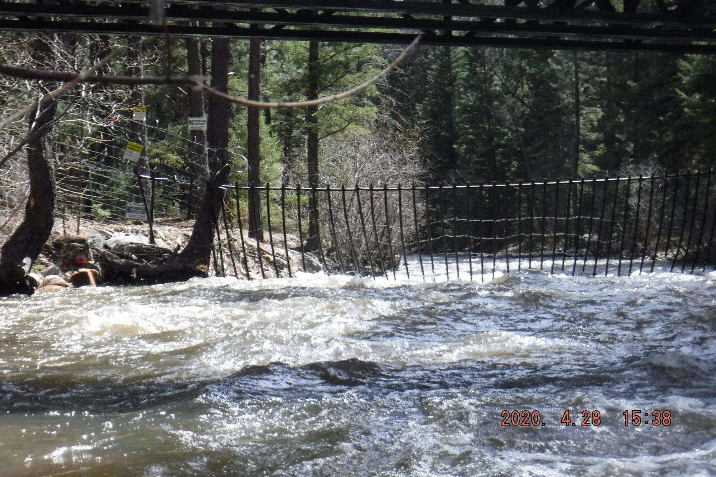 """Fencing and razor wire are strung across the Pecos River on the Hersh property. """"No Trespassing"""" signs hang on nearby trees."""