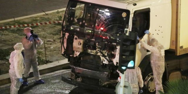 Authorities investigate a truck after it plowed through Bastille Day revellers in the French resort city of Nice, southern France, on July 14, 2016. France's counterterrorism prosecutors have requested nine suspects to be sent to trial in connection with the attack in Nice that left 86 people dead.<br> (Sasha Goldsmith via AP, File)