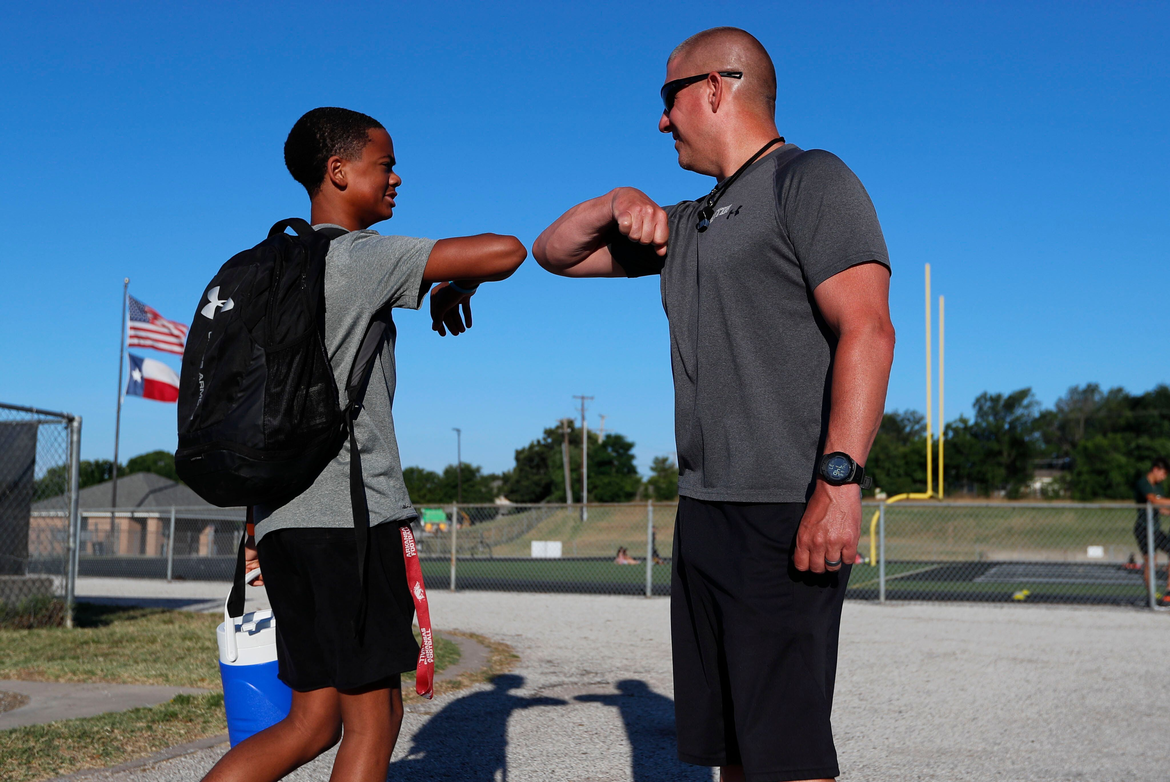 Head football coach Bob Wager, right, and sophomore safety Cameron Conley greet each other at the re-opening of strength and