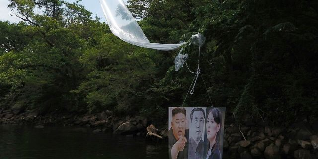 A balloon carrying a banner with images of North Korean leader Kim Jong Un, left, the late leader Kim Il Sung, center, and Kim Yo Jong, the powerful sister of Kim Jong Un, released by Fighters For Free North Korea, is seen in Hongcheon, South Korea, on Tuesday. (Yang Ji-woong/Yonhap via AP)
