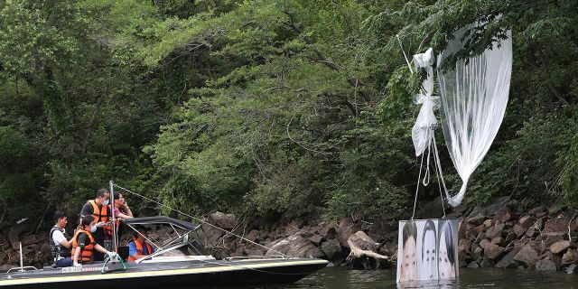 Police officers ride a boat to collect a balloon carrying a banner with images of North Korean leader Kim Jong Un, the late leader Kim Il Sung and Kim Yo Jong, the powerful sister of Kim Jong Un, in Hongcheon, South Korea, on Tuesday. (Yang Ji-woong/Yonhap via AP)
