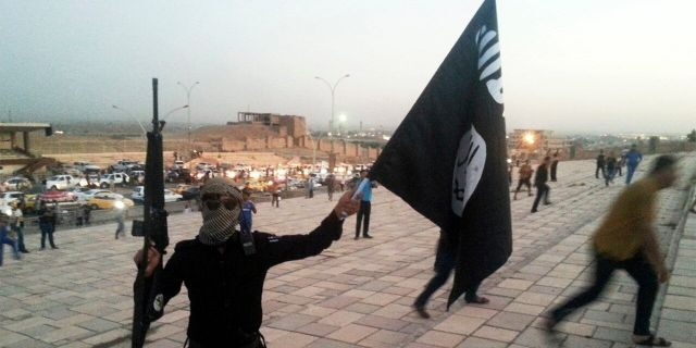 A fighter of the Islamic State of Iraq and the Levant (ISIL) holds an ISIL flag and a weapon on a street in the city of Mosul, June 23, 2014. REUTERS/Stringer