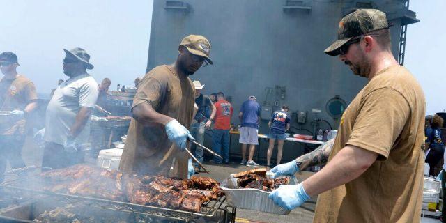 Sailors participate in a steel beach picnic on the flight deck of the aircraft carrier USS Dwight D. Eisenhower on June 6, 2020.<br> (Mass Communication Specialist Seaman Brennen Easter/U.s. Navy via AP)