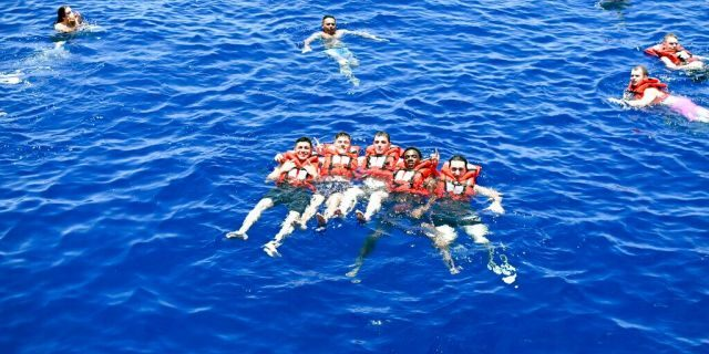 Sailors assigned to the guided-missile cruiser USS San Jacinto pose for a photo on May 17, 2020, during a swim call in the Persian Gulf. (Mass Communication Specialist 2nd Class Maxwell Anderson/U.S. Navy via AP)