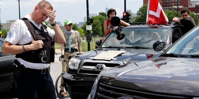 A Chicago police officer wiping his face at a Health Care Justice rally in Chicago on Saturday.