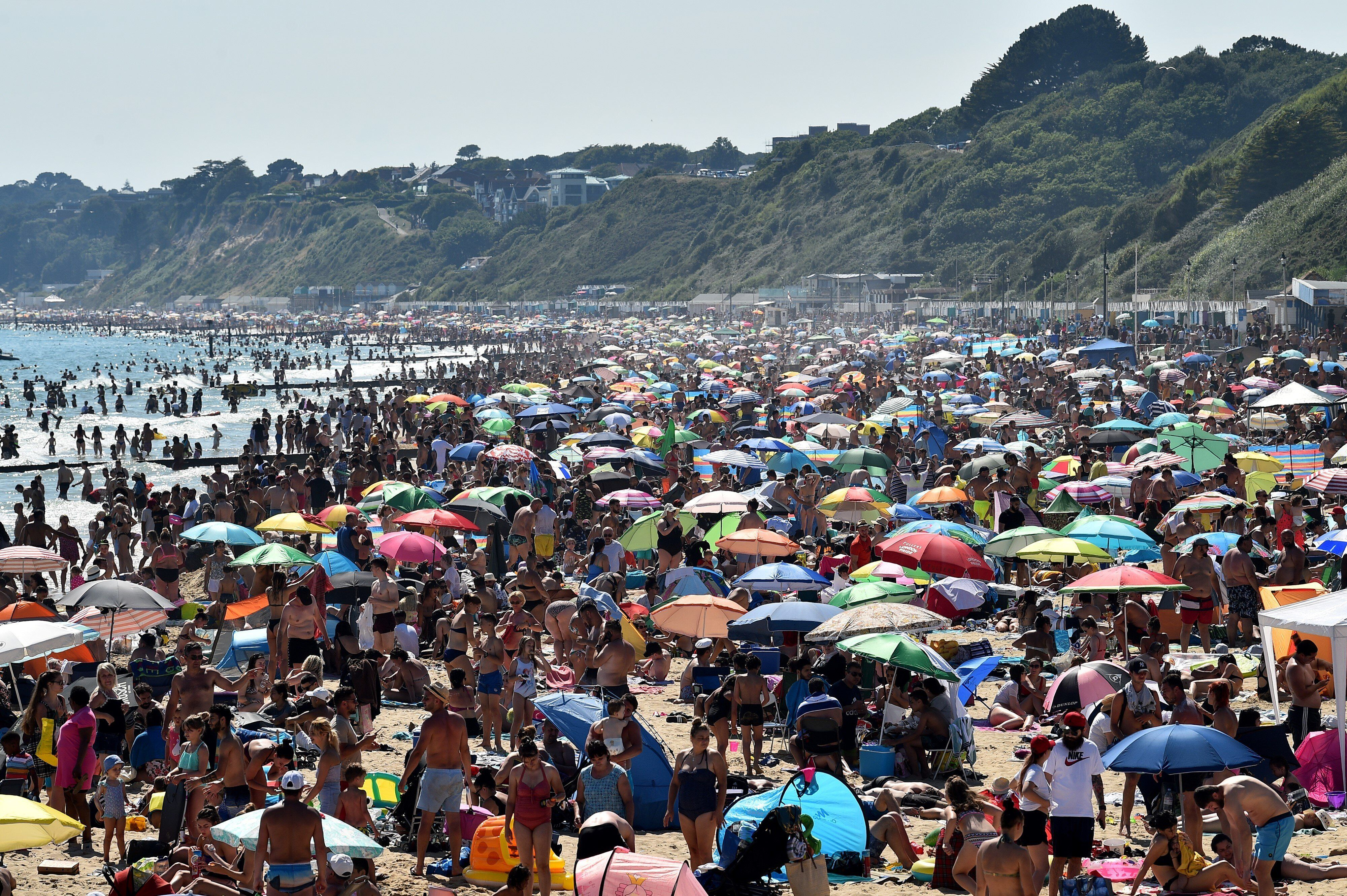 Beachgoers enjoy the sunshine as they sunbathe and swim on Bournemouth Beach in southern England on June 25.