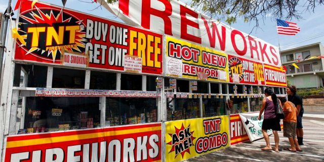 In this July 2, 2013, file photo, a family purchases fireworks at a TNT Fireworks stand in the City of Monterey Park, Calif. With fewer professional celebrations on July 4, 2020, due to the coronavirus pandemic, many Americans are bound to shoot off fireworks in backyards and at block parties. And they already are: Sales have been booming. (AP Photo/Nick Ut, File)